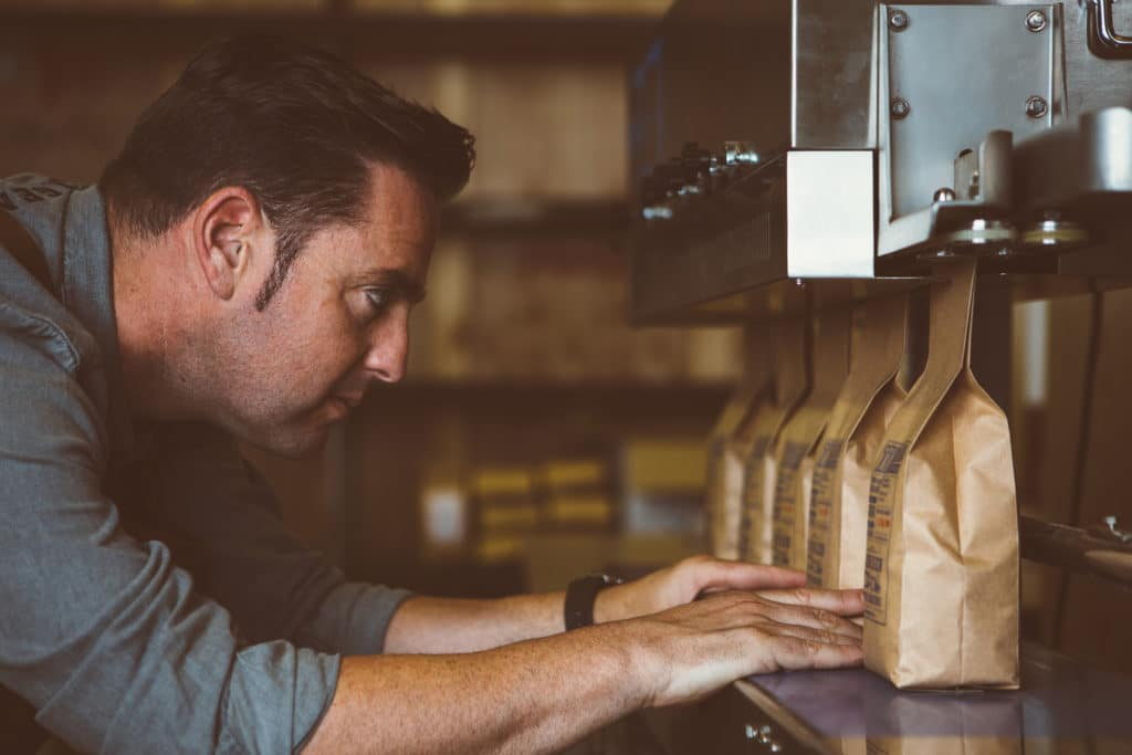Side view of adult man looking at row of packages of roasted beans